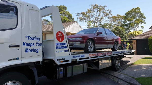 A 90's model holden being picked up by a tilt tray tow truck