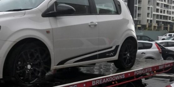 A car with a flat tyre and other things wrong with it on the back of a Fast Sydney Tow Truck.