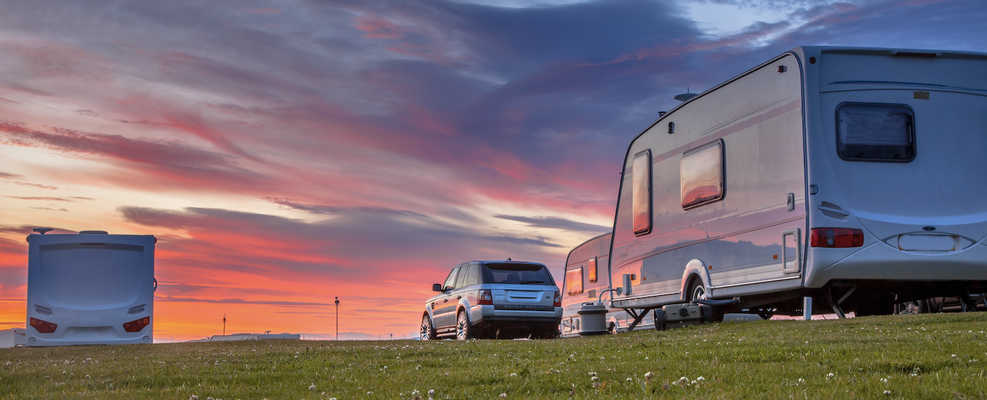 A car towing a caravan on the grass with a sunset.