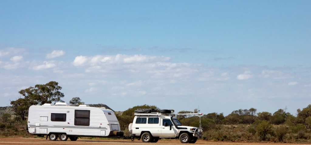 Toyota Land Cruiser towing a caravan in the outback.